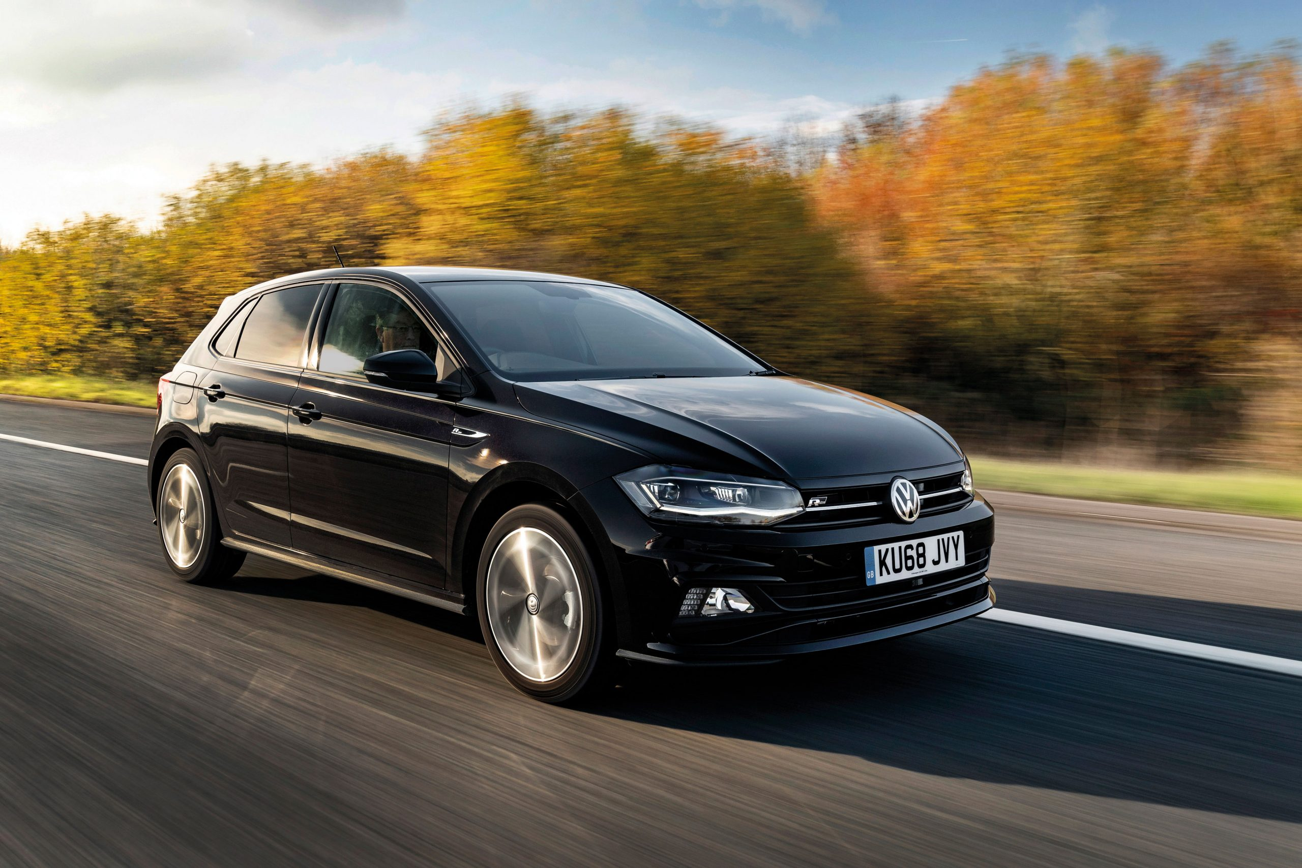 VW Polo, in black driving along a country road