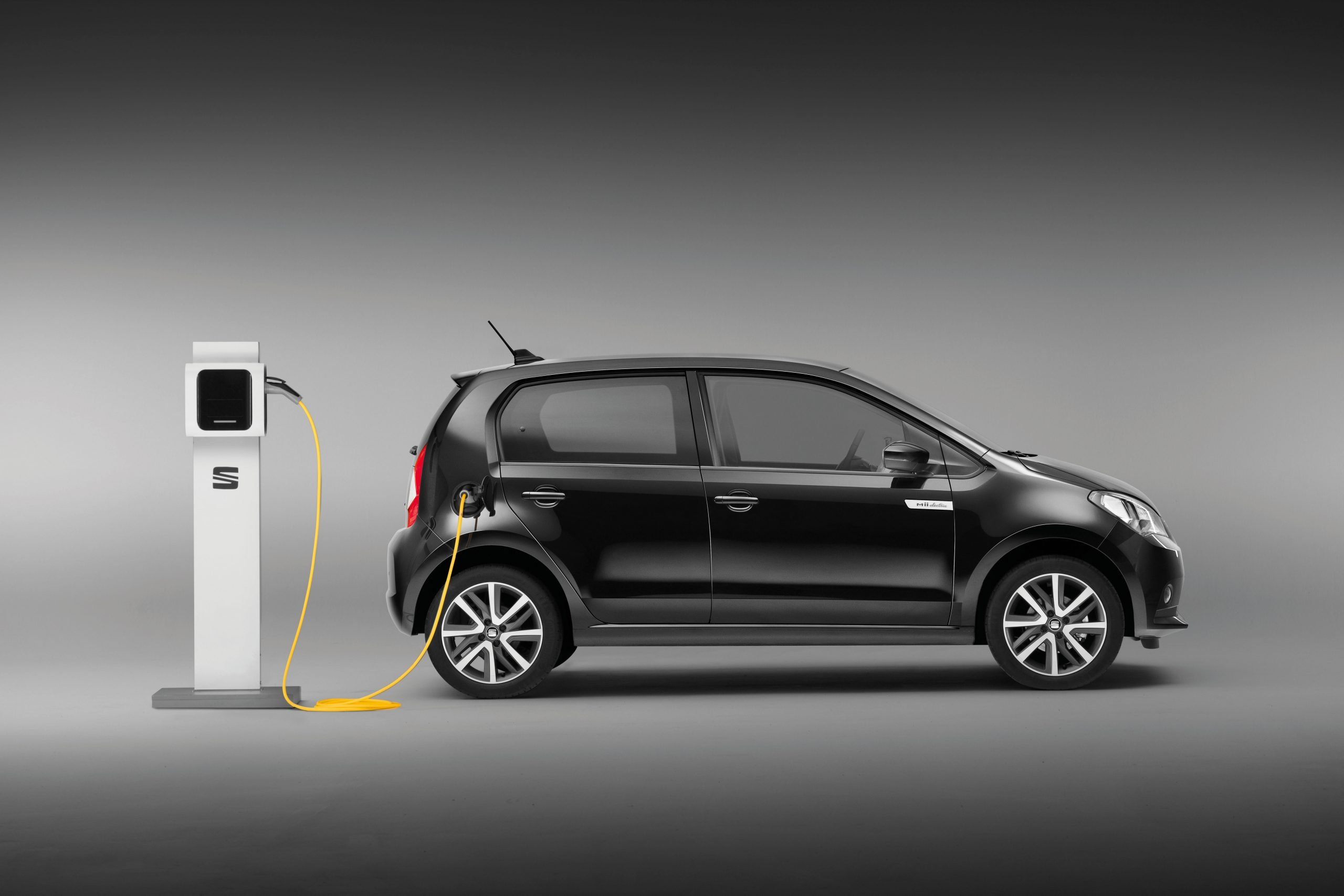 Seat Mii Electric, in black, charging at an electric car charging point