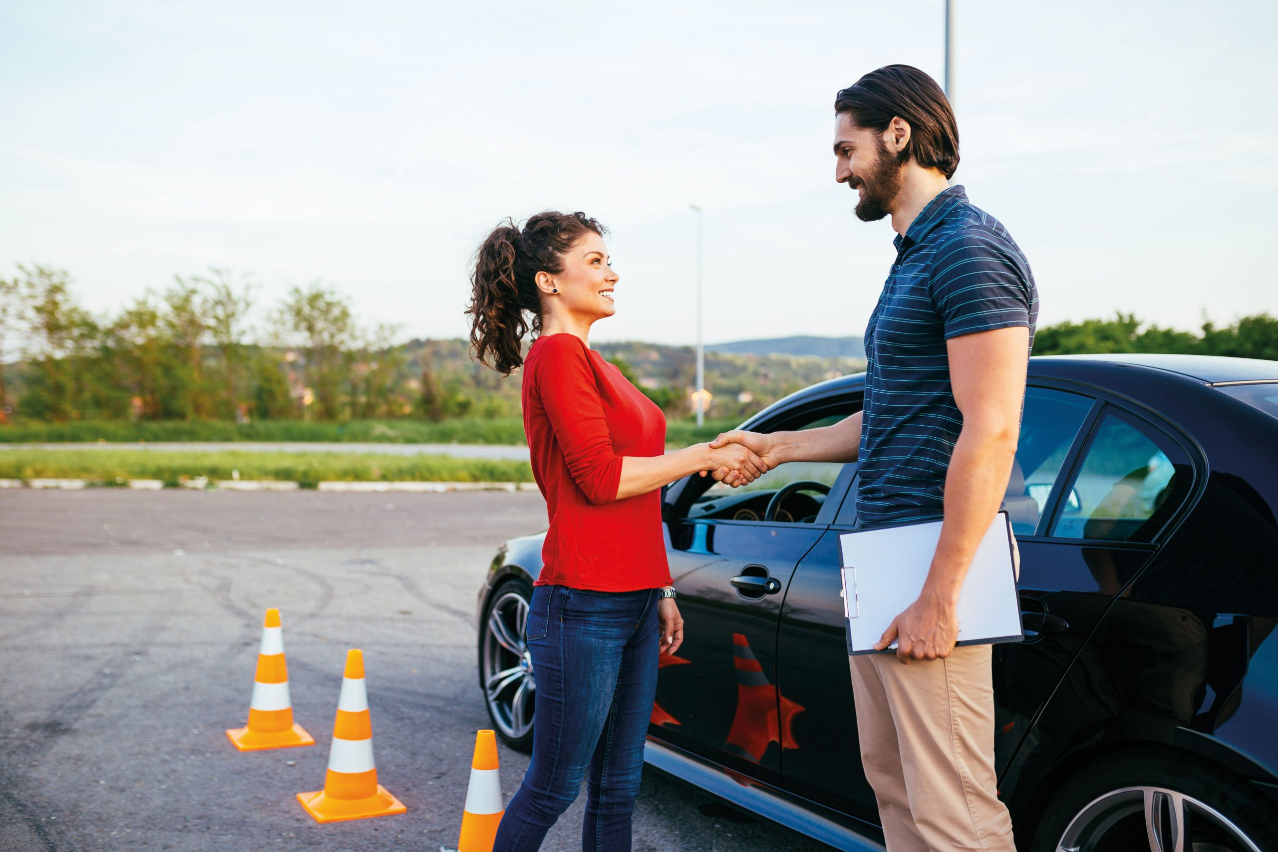 Man and woman shaking hands while standing next to a car after doing a training course in professional development