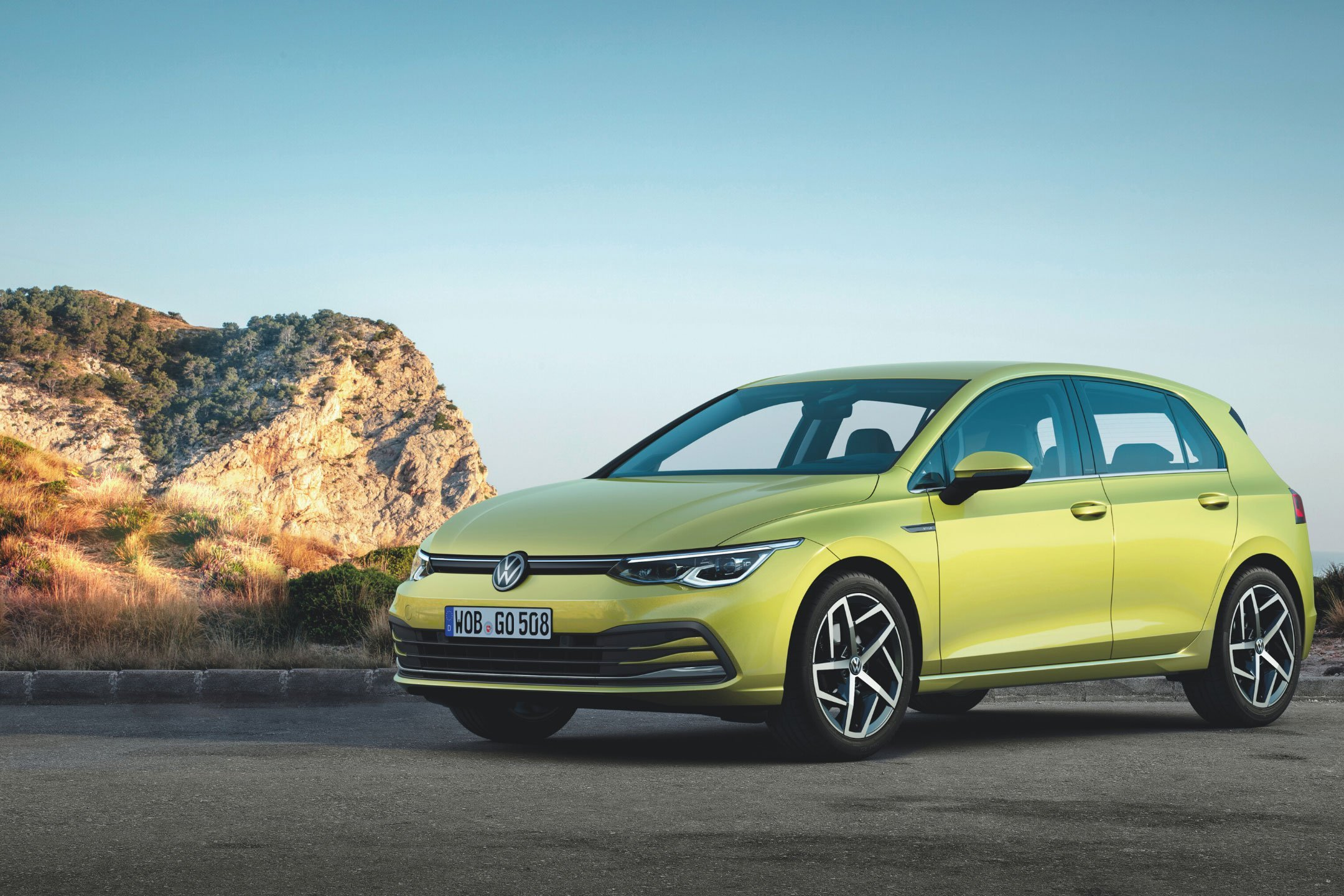 Lime coloured Volkswagen Golf Mk8 parked with the ocean behind it